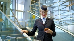 Stewardess with glasses reading a message on your phone and smiling Stock Footage
