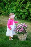 Little girl stands near a basket of flowers Stock Photos