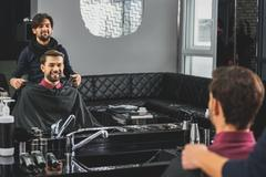 Skillful barber preparing client for haircut Stock Photos