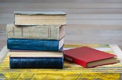 Stack of hardback books on wooden table. English textbook. Kuvituskuvat