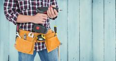 Mid section of handyman with tool belt and drill machine Stock Photos