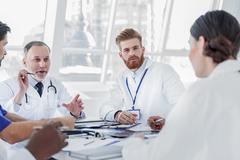 Serious medical team discussing human health Stock Photos