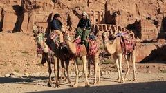 Jordanians on camels near Royal Tombs in Petra, Jordan Stock Footage