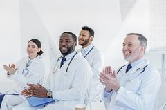 General practitioners applauding to successful lecturer Stock Photos