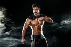Severe barbarian in leather costume with sword in smoke Stock Photos
