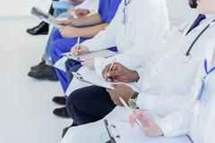 Professional general practitioners making notes at clinic Stock Photos