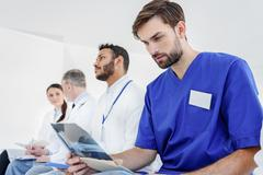 Serious general practitioner looking at radiograph Stock Photos
