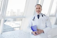 Mature doctor is happy about successful results of cure Stock Photos