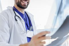 Male physician is satisfied with roentgen picture Stock Photos