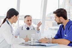 Mature general practitioner explaining something to interns Stock Photos