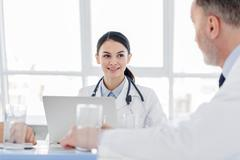 Professional general practitioners talking at clinic Stock Photos