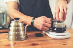 Bartender making hot beverage in specific cup Stock Photos