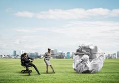 Businesspeople pulling with effort big crumpled ball of paper as creativity sign Stock Photos