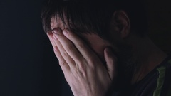 Grief, man covering face and crying, low key portrait Stock Footage