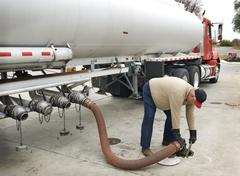 Fuel Delivery Operator Fills Underground Tank With Hose Stock Photos