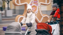 Two young cheerful girlfriends shopping with baby carriages at christmas eve Stock Footage