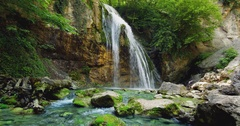Mountain Waterfall Water Flows Over Green and Yellow Rocks, the Water Diverges Stock Footage