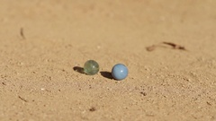Kids playing marbles at sand Stock Footage
