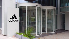Street signage board with Adidas logo. Modern office building. Editorial 4K 3D Stock Footage
