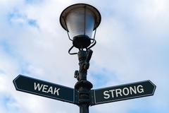 Weak versus Strong directional signs on guidepost Stock Photos
