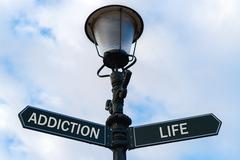 Addiction versus Life directional signs on guidepost Stock Photos