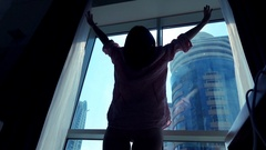 Young woman stretching arms and admire view from the window at home, super slow Stock Footage