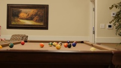 Dolly shot of playing pool lady playing pool in retirement home Stock Footage
