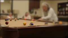 Shot of a women playing pool in a retirement home Stock Footage