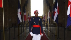 A young soldier stands between the Dominican flag Stock Footage