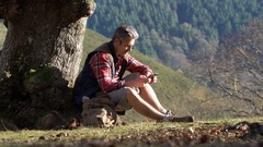 Hiker relaxing by tree on a fall journey Stock Footage