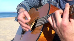 Closeup of man playing the guitar on the beach Stock Footage