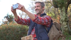 Hiker taking picture with smartphone during hiking journey Stock Footage