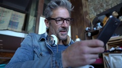 Mature guy with eyeglasses connected on smartphone in bar Stock Footage