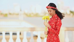 Beautiful Vietnamese girl in red traditional dress Ao Dai with yellow flowers Stock Footage