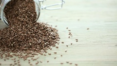 Flax seeds on painted wood board. Stock Footage