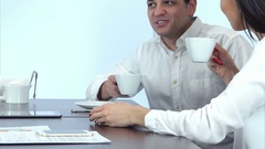 Two friendly coworkers talking and drinking coffee in a cafe Stock Footage