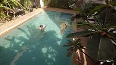 Mother and Baby Swimming in Pool on Sunny Day Stock Footage