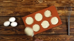 Woman cooking muffins and putting dough into orange silicon baking form Stock Footage