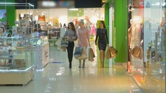 Three Girls are walking near store windows in Shopping Mall. Steadicam shot Stock Footage