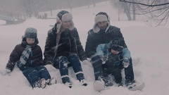 Family sitting on the snow. Two boys and there parents. Mama making snowballs. Stock Footage