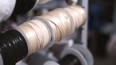 Female hand slowly pull beige webbing from the spool in the rack Stock Footage