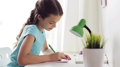 Happy girl with book writing to notebook at home Stock Footage