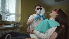 Female patient getting treatment with dental UV light equipment. Dental office Stock Footage
