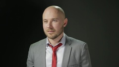 Bald man with a beard in a suit looks to the side and corrects red tie. on a Stock Footage