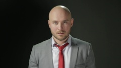 Bald man with a beard in a suit looks to the camera and corrects red tie. on a Stock Footage