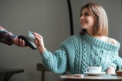 Cheerful young lady pays for her order with debit card. Stock Photos