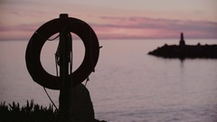 Life Preserver on pole at beach at sunset. Horizontally framed shot. Stock Footage