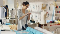 Beautiful Brunette Fashion Designer Lays Out Templates on the fabrics Stock Footage