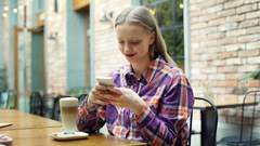 Happy girl in checked shirt sitting in the cafe and texting on smartphone Stock Footage