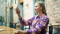 Pretty girl in checked shirt looking happy while doing photos in the cafe Stock Footage